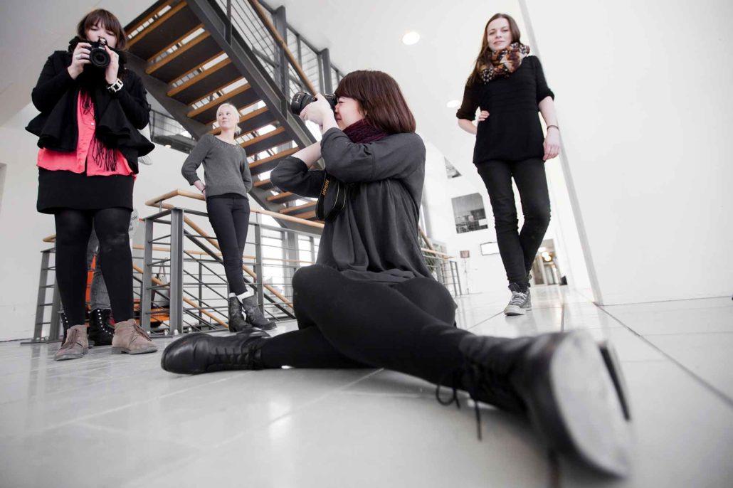 Deltagere på fotokursus hos Visuelmedie øver sig.