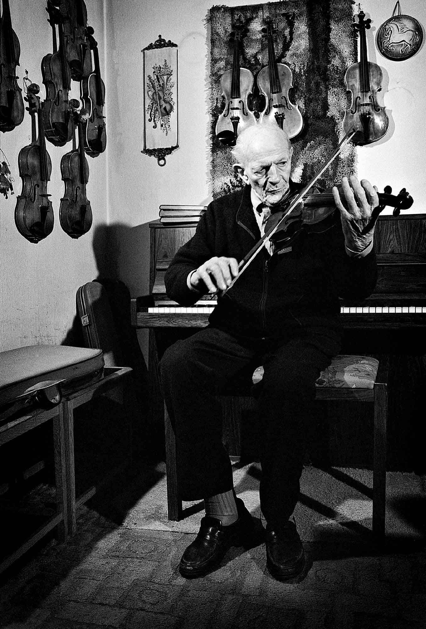 gammel mand spiller på en af hans 10 hjemmebyggede violiner