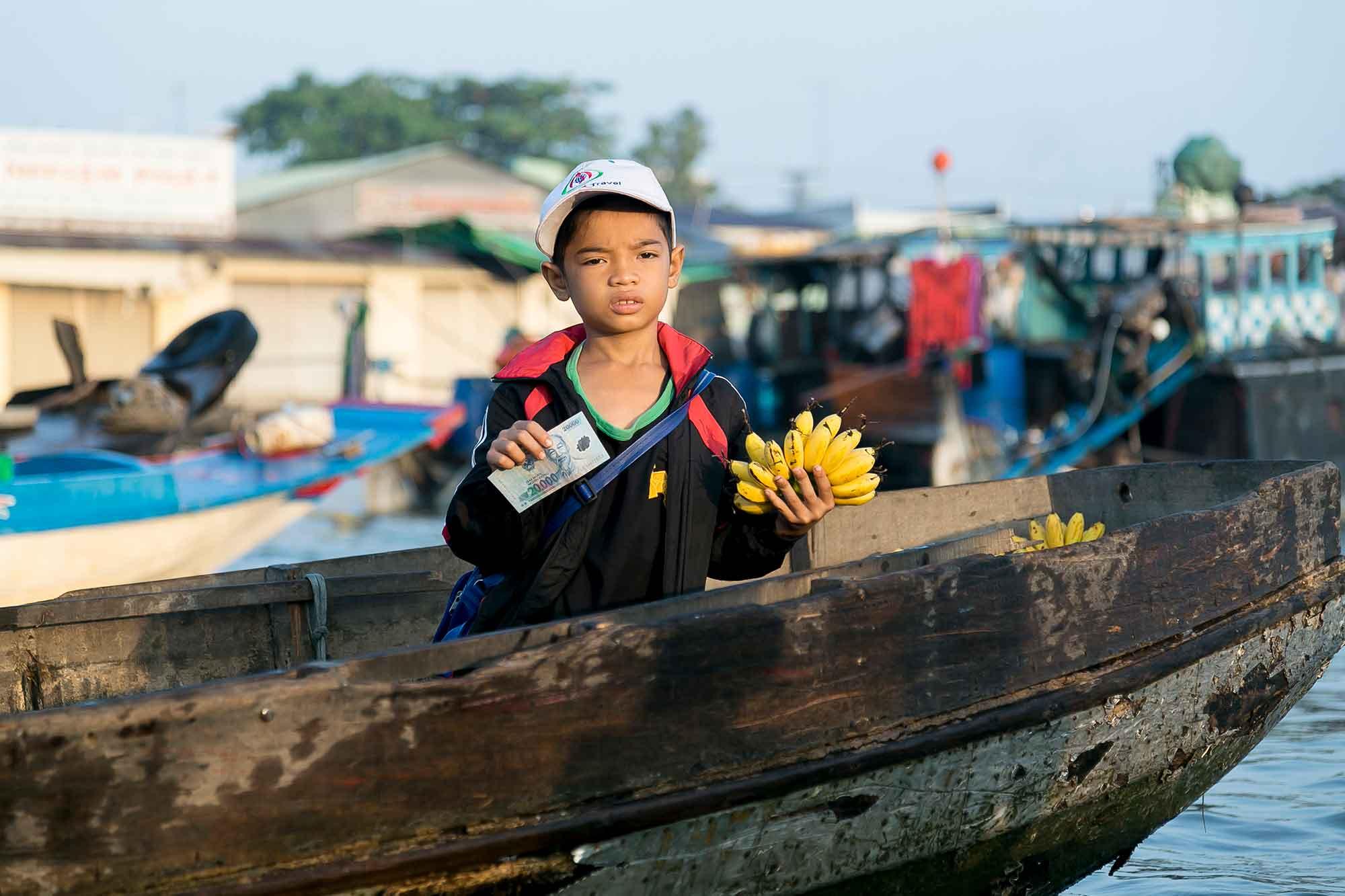 Vietnam-dreng sælger bananer på vandmarked